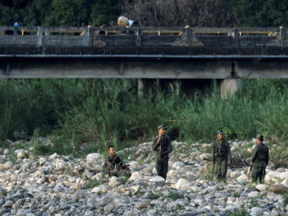 """Venezuelan soldiers guard """"trochas"""" -illegal trails- used by people to cross from San Antonio del Tachira, in Venezuela, to Cucuta, in Colombia, near the Simon Bolivar international bridge, on May 1, 2019. (Photo by Luis ROBAYO / AFP) (Photo credit should read LUIS ROBAYO/AFP/Getty Images)"""