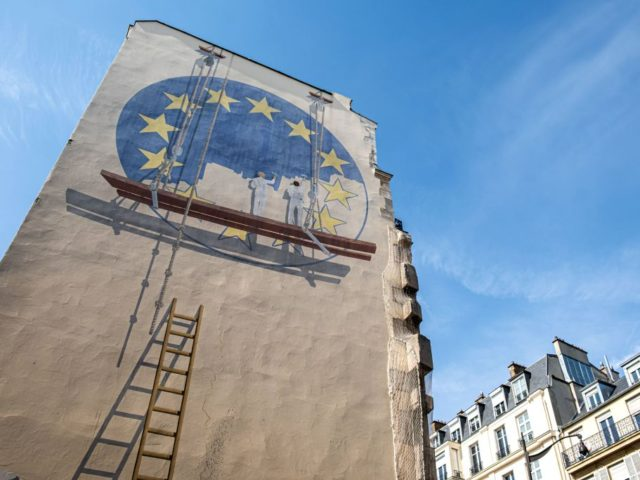 TOPSHOT - A trompe l'oeil shows two workers painting the European Union flag on the side of a building in the French capital Paris on May 23, 2019. - Europe kicked off voting across the continent in a contest in which rising populist forces are hoping to make significant gains, …