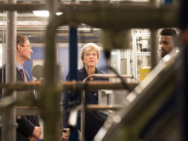 British Prime Minister Theresa May visits Imperial College in London where she was shown machinery which converts carbon dioxide into oxygen after her announcement that the UK is to set a legally binding target to end its contribution to climate change by 2050 on June 12, 2019. (Photo by Stefan …