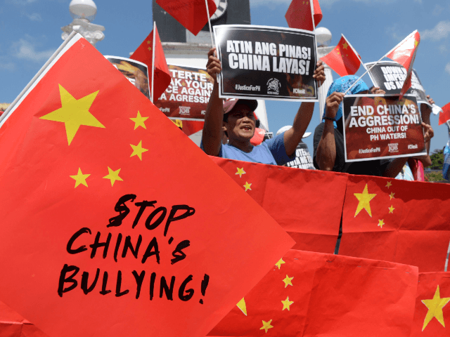 Activists display anti-China placards and flags during a protest at a park in Manila on June 18, 2019, after a Chinese vessel last week collided with a Philippine fishing boat which sank in the disputed South China Sea and sailed away sparking outrage. - The sinking of the Filipino fishing …