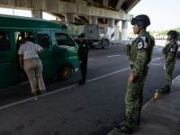 Members of the National Guard stand as an immigration officer check's passengers' documents at a checkpoint on June 18, 2019 on a highway in Tuxtla Chico, Mexico. The Mexican government launched a deployment of the National Guard seeking to control the flux of migrants crossing from Guatemala to Mexico, as …