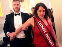 "LONDON, ENGLAND - JUNE 20: Climate change protester is escorted out after interrupting British Chancellor of the Exchequer Philip Hammond's speech during the annual Mansion House dinner on June 20, 2019, in London, England. Greenpeace volunteers wearing red evening dress with sashes reading ""climate emergency"" gatecrashed and disrupted the beginning …"