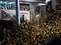 A group of police officers in riot gear (L) stand by at the police headquarters as protesters gather outside the building in Hong Kong on June 21, 2019. - Thousands of protesters converged on Hong Kong's police headquarters on June 21, demanding the resignation of the city's pro-Beijing leader and …