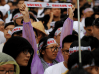 "Thousands of protesters hold placards with messages ""reject red media and safe guard the nation's democracy"" during a rally on Ketagalan Boulevard in front of the presidential office building in Taipei on June 23, 2019. - A rally against pro-Beijing Taiwanese media was held, with tens of hundreds of people …"