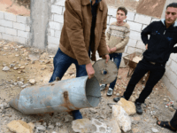 A Syrian man shows a cluster bomb, that releases or ejects smaller sub-munitions, in the northern Syrian town of Taftanaz, in the Idlib province, on November 9, 2012. Syrian President Bashar al-Assad said his future could only be decided at the ballot box and denied Syria was in a state …