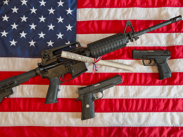 This February 4, 2013 photo illustration in Manassas, Virginia, shows a Colt AR-15 semi-automatic rifle a Colt .45 semi-auto handgun and a Walther PK380 semi-auto handgun and a copy of the US Constitution on top of the American flag. US President Barack Obama Monday heaped pressure on Congress for action …