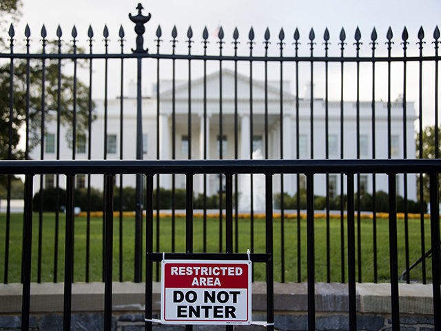 A sign warning of a restricted area is posted on the temporary barricade in front of the fence line to the White House in Washington, DC, October 23, 2014. A suspect who climbed over the White House fence on October 22 was nabbed by Secret Service agents and dogs, a …