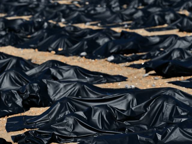An Amnesty International supporter is pictured in a 'body bag' on Brighton beach in southern England, on April 22, 2015, during a photocall by Amnesty International to highlight what they claim is Britain's shameful response to the refugee and migrant crisis in the Mediterranean. Around 50 supporters of the London-based …