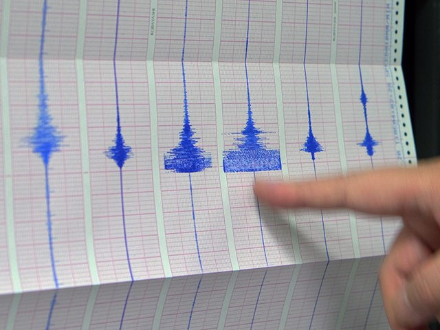 A staff member of the Seismology Center, points on a chart of the earthquake activity detected by the central Weather Bureau in Taipei on February 22, 2014. A 5.4-magnitude earthquake jolted northeastern Taiwan early on February 22, the Seismology Centre said, but there were no immediate reports of casualties or …