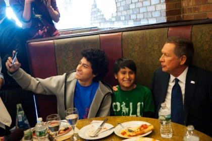 NEW YORK - MARCH 30: GOP Presidential Candidate John Kasich (right) poses with two children at Gino's Pizzeria and Restaurant on March 30, 2016 in the Queens borough of New York City. Kasich is one of three remaining GOP Presidential Candidates fighting for New York's 95 Republican delegates in the …