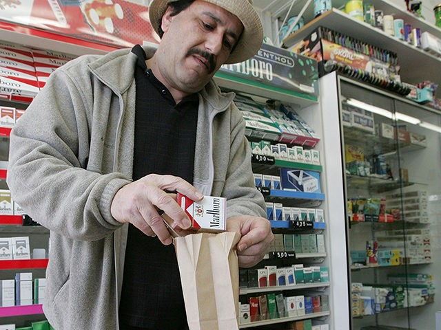SAN FRANCISCO - MARCH 09: Shop owner Izzat Asfour sells a pack of cigarettes to a customer March 9, 2006 in San Francisco. Sales of cigarettes in the U.S. in 2005 hit a 55-year low, falling more than 21 percent since state attorneys general negotiated an historic settlement with the …