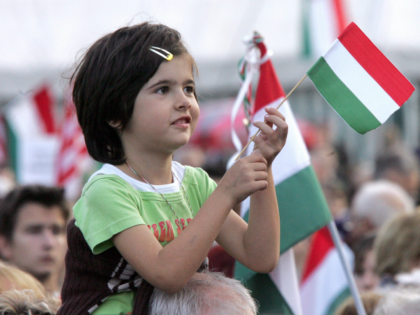 Budapest, HUNGARY: Sitting on his father's back, a girl waves a national flag on Kossuth square in front of the Parliament in Budapest, 13 October 2006. Opposition chief Viktor Orban demanded Gyurcsany's resignation ever since a recording was leaked on September 17 in which the prime minister said the government …