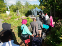 TOPSHOT - A long line of asylum seekers wait to illegally cross the Canada/US border near Champlain, New York on August 6, 2017. - In recent days the number of people illegally crossing the border has grown into the hundreds. (Photo by Geoff Robins / AFP) (Photo credit should read …