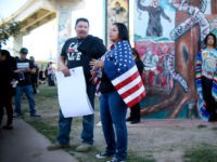 "A Hispanic woman stands draped in the American flag opposite a ""Patriot Picnic"" demonstration at Chicano Park on February 3, 2018 in San Diego. / AFP PHOTO / SANDY HUFFAKER (Photo credit should read SANDY HUFFAKER/AFP/Getty Images)"