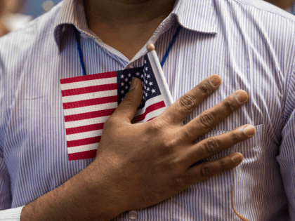 NEW YORK, NY - JULY 3: A new U.S. citizen holds a flag to his chest during the Pledge of Allegiance during a naturalization ceremony at the New York Public Library, July 3, 2018 in New York City. 200 immigrants from 50 countries became citizens during the ceremony, one day …