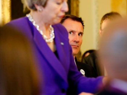 Britain's Health Secretary Jeremy Hunt (R) looks on as Britain's Prime Minister Theresa May speaks to assembled guests as she hosts a reception to mark the 70th Anniversary of the NHS, at 10 Downing Street, in central London on July 4, 2018. (Photo by Tolga AKMEN / POOL / AFP) …