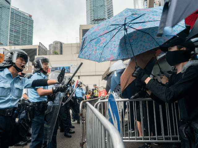Police officers stand guard as protesters block a street near the government headquarters during a rally against the extradition bill on June 12, 2019 in Hong Kong, China. Large crowds of protesters gathered in central Hong Kong as the city braced for another mass rally in a show of strength …