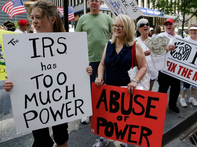 In this May 21, 2013, file photo, tea party activists demonstrate on Fountain Square before marching to the John Weld Peck Federal Building in Cincinnati to protest the Internal Revenue Service's targeting of conservative groups seeking tax-exempt status. On Wednesday, April 4, 2018, a federal judge gave preliminary approval to …