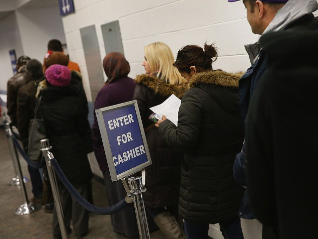 CHICAGO, IL - DECEMBER 10: Illinois residents wait in line at a driver services facility on December 10, 2013 in Chicago, Illinois. Illinois recently began a Temporary Visitors Driver's License (TVDL) program which allows undocumented immigrants to obtain a driver's license. The applicants must have an Illinois address, prove 12 …