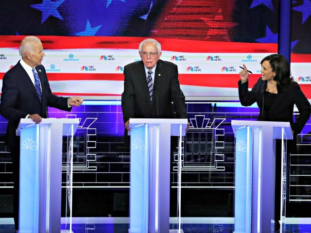 MIAMI, FLORIDA - JUNE 27: Sen. Kamala Harris (R) (D-CA) and former Vice President Joe Biden (L) speak as Sen. Bernie Sanders (I-VT) looks on during the second night of the first Democratic presidential debate on June 27, 2019 in Miami, Florida. A field of 20 Democratic presidential candidates was …
