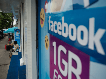The Facebook logo is seen on an advertisement by a local telecom company in Yangon on June 7, 2018. - Facebook has blacklisted a group of Myanmar Buddhist hardliners including monks notorious for bilious hate speech against Rohingya Muslims, the company said June 7, as it scrambles to show it …