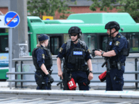Policemen stand guard outside the central train station after a man threatened to detonate a bomb in Malmö in southern Sweden on June 10, 2019. - The station building was evacuated due to alarms about a suspected object. The man was wounded by police and his bag destroyed by deminers. …
