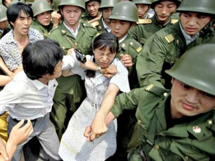 A woman is caught between civilians and soldiers, who were trying to remove her from an assembly near the Great Hall of the People in Beijing on June 3, 1989. (Jeff Widener / Associated Press)