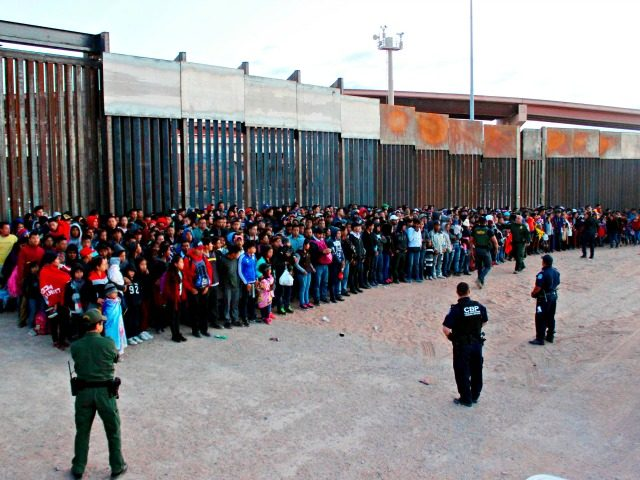 This May 29, 2019 photo released by U.S. Customs and Border Protection (CBP) shows some of 1,036 migrants who crossed the U.S.-Mexico border in El Paso, Texas, the largest that the Border Patrol says it has ever encountered. Video shows them going under a chain-link fence to the U.S., where …