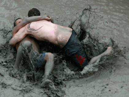 BORYEONG, SOUTH KOREA - JULY 17: Participants wrestle in the mud during the 13th Annual Boryeong Mud Festival at Daecheon Beach on July 17, 2010 in Boryeong, South Korea. Now in its 13th year, the festival features mud wrestling, mud sliding and a mud king contest. (Photo by Chung Sung-Jun/Getty …