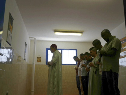 """In this photo taken on Friday, June 23, 2017, inmates pray with the Imam Mimoun El Hachmi, left, inside the Terni penitentiary. Stunned that Berlin market attack suspect spent time in Italian jails, Italy turns to """"moderate"""" imams to discourage radicalization among Muslim inmates. (AP Photo/Gregorio Borgia)"""