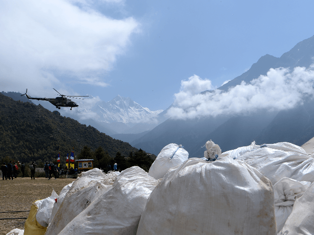 A Nepali Army helicopter flies over waste collected from Mount Everest at Namche Bazar in Solukhumbu district on May 27, 2019, before it is transported to Kathmandu to be recycled. - Some ten tonnes of garbage have been picked from Mount Everest and four bodies retrieved at the end of …