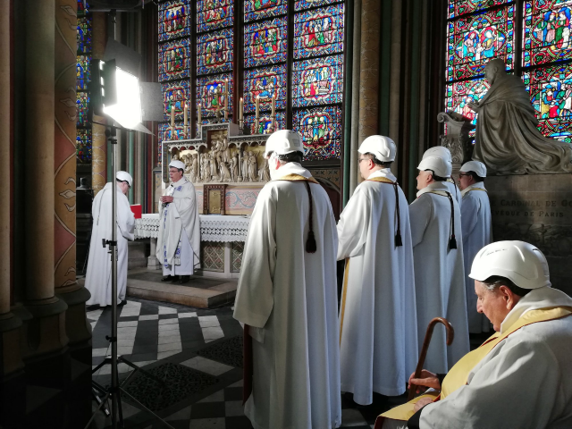 The Archbishop of Paris Michel Aupetit, second left, leads the first mass in a side chapel, two months after a devastating fire engulfed the Notre-Dame de Paris cathedral, Saturday June 15, 2019, in Paris. (Karine Perret, Pool via AP)