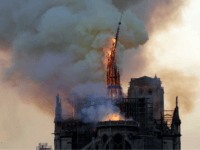 TOPSHOT - The steeple and spire of the landmark Notre-Dame Cathedral collapses as the cathedral is engulfed in flames in central Paris on April 15, 2019. - A huge fire swept through the roof of the famed Notre-Dame Cathedral in central Paris on April 15, 2019, sending flames and huge …