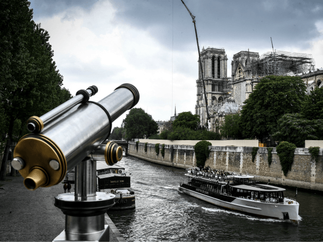 A fly boat cruises along the River Seine past the Notre-Dame de Paris Cathedral, which was badly damaged by a huge fire on April 15, and which is under repair, on May 20, 2019, in the French capital Paris . (Photo by STEPHANE DE SAKUTIN / AFP) (Photo credit should …