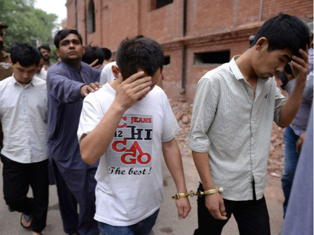 A Pakistani Federal Investigation Agency (FIA) official (3rd L) and a policeman escort to a court handcuffed Chinese nationals accused of allegedly luring young Pakistani girls into fake marriages then forcing them into prostitution in China, on May 11, 2019, in Lahore. - Human Rights Watch raised the alarm over …