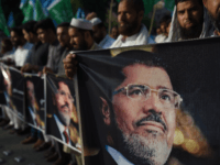 "Activists of Jamaat-e-Islami hold pictures of former Egyptian President Mohamed Morsi during a symbolic funeral ceremony in Islamabad on June 18, 2019. - The UN human rights office called on June 18 for an ""independent inquiry"" into former Egyptian president Mohamed Morsi's death while in state custody. (Photo by FAROOQ …"