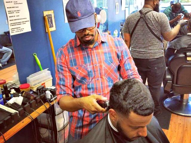Percy Craig cuts a customer's hair.