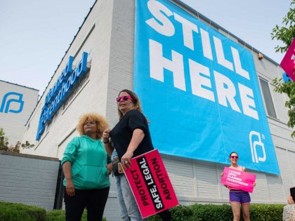 Pro-choice supporters pose for photos outside the Planned Parenthood Reproductive Health Services Center in St. Louis, Missouri, May 31, 2019, the last location in the state performing abortions, after a US Court announced the clinic could continue operating. - A US Court on May 31, 2019 blocked Missouri from closing …