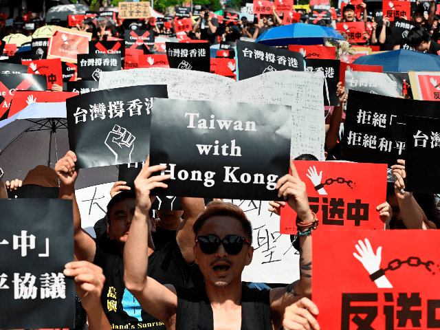 Protesters display placards during a demonstration in Taipei on June 16, 2019, in support of the continuing protests taking place in Hong Kong against a controversial extradition law proposal. - Tens of thousands of people rallied in central Hong Kong on Sunday as public anger seethed following unprecedented clashes between …