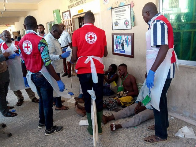 EDITORS NOTE: Graphic content / Red Cross officials attend to victims of a triple suicide bombing, in Konduga, 38 kilometres (24 miles) from the Borno state capital Maiduguri, northeast Nigeria, on June 17, 2019. - Thirty people were killed late on June 16 in a triple suicide bombing in northeast …