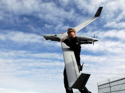 Flight test pilot Alex Gustafson carries an Insitu ScanEagle unmanned aircraft in preparation for a flight in Arlington, Ore., Tuesday, March 26, 2013.(AP Photo/Don Ryan)