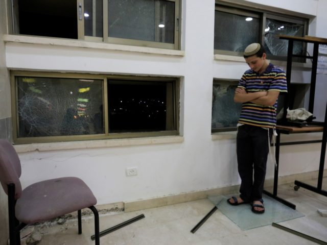 A student stands inside a Jewish religious school in Sderot, Israel, after it was hit by a rocket fired from the Gaza Strip, Thursday, June 13, 2019. (AP Photo/Tsafrir Abayov)
