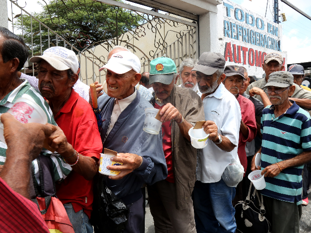 Men stand in line outside Doris Ortegano's house waiting for what may be their only meal for the day on May 13, 2019 in Barquisimeto, Venezuela. One year ago, Doris Ortegano started cooking an giving away food for people in need in Barquisimeto, Lara. According to her words, she asked …