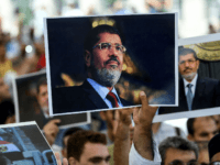 People hold picture of Egyptian President Mohamed Morsi during a symbolic funeral cerenomy on June 18, 2019 at Fatih mosque in Istanbul. - Thousands joined in prayer in Istanbul on Tuesday for former Egyptian president Mohamed Morsi who died the previous day after collapsing during a trial hearing in a …