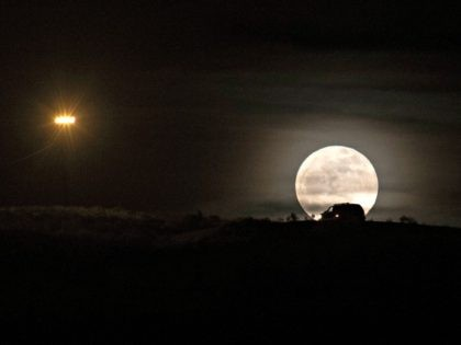A full moon rises over the US-Mexico border as a border protection vehicle patrols the area, as seen from Tijuana, Baja California state, Mexico on December 22, 2018. - US politicians rebooted tense budget talks Saturday after their failure to pass a federal spending bill triggered a partial government shutdown, …