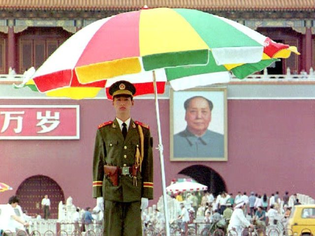 BEIJING, CHINA - JUNE 3: A People's Liberation Army(PLA) soldier stands guard under an umbrella at Tiananmen Square 03 June. In addition to uniformed troops, plainclothed police reinforce security one day prior to the fourth anniversary of the Jun 1989 massacre of pro-democracy activists here. AFP PHOTO (Photo credit should …