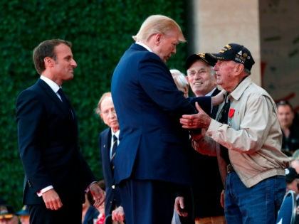 US President Donald Trump (C) and French President Emmanuel Macron (L) greet a US veteran during a French-US ceremony at the Normandy American Cemetery and Memorial in Colleville-sur-Mer, Normandy, northwestern France, on June 6, 2019, as part of D-Day commemorations marking the 75th anniversary of the World War II Allied …