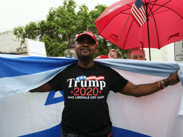 Trump supporters wave a US flag with one wrapped in an Israeli flag as they counter a demonstration against the State Visit of US President Donald Trump in central London on June 4, 2019, on the second day of Trump's three-day State Visit to the UK. - US President Donald …
