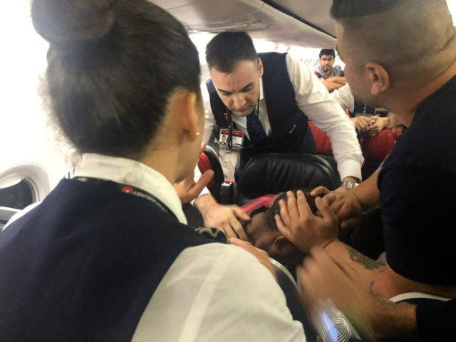 The scene as Associated Press photographer Hussein Malla observes as passengers and crew aboard a Turkish Airlines jetliner subdue a man who started screaming a few minutes after takeoff from Istanbul. Turkey, Friday June 14, 2019. The unidentified man began smashing at an oxygen mask box and damaged a cabin …