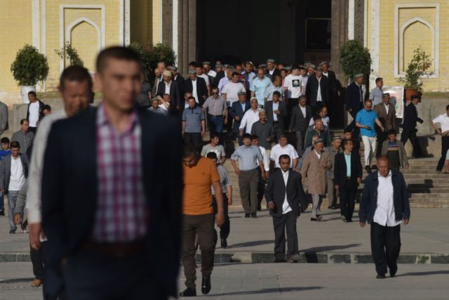 Uighur men leave after Eid al-Fitr prayers, marking the end of Ramadan, at the Id Kah mosque in Kashgar, in China's western Xinjiang region early on June 5, 2019. (Photo by GREG BAKER / AFP) (Photo credit should read GREG BAKER/AFP/Getty Images)